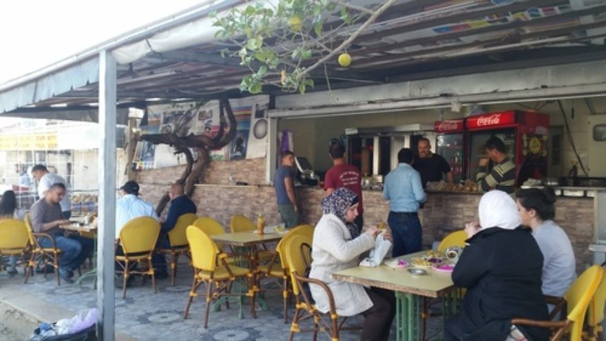 Click photo to download. Caption: Israeli Jews and Palestinian Arabs eat lunch at a falafel joint in an Arab strip mall in Ariel, where JNS.org asked Palestinians for their reactions to the Israeli election. Credit: Orit Arfa.
