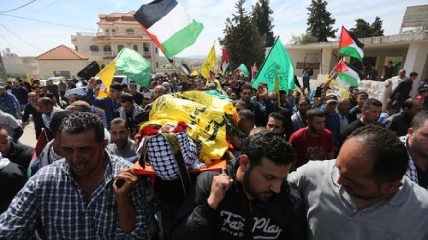 In March 2016 in the West Bank village of Deir Debwan, Palestinian mourners chant slogans while carrying the body of Mahmoud Shalan, a Palestinian-American terrorist who had tried to murder Israelis before security forces killed him. Credit: Photo by Flash90.