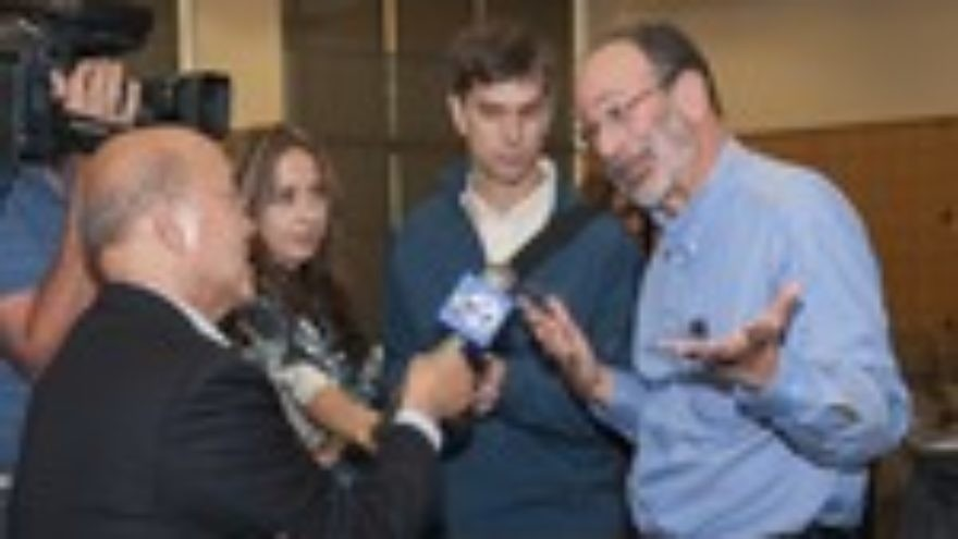Click photo to download. Caption: Nobel laureate Alvin Roth, right, speaks with ABC reporter David Louie, left, after a press conference on his prize. Credit: Linda A. Cicero/Stanford News Service.