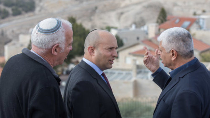 Jewish Home Party leader Naftali Bennett (center) speaks with Ma'ale Adumim Mayor Benny Kasriel (right) before the start of a special Jewish Home faction meeting on Jan. 2, 2018. Bennett has advocated for a Knesset bill to be introduced after president-elect Donald Trump takes office on Jan. 20 calling, for Israel's annexation of Ma'ale Adumim. Credit: Yonatan Sindel/Flash90.