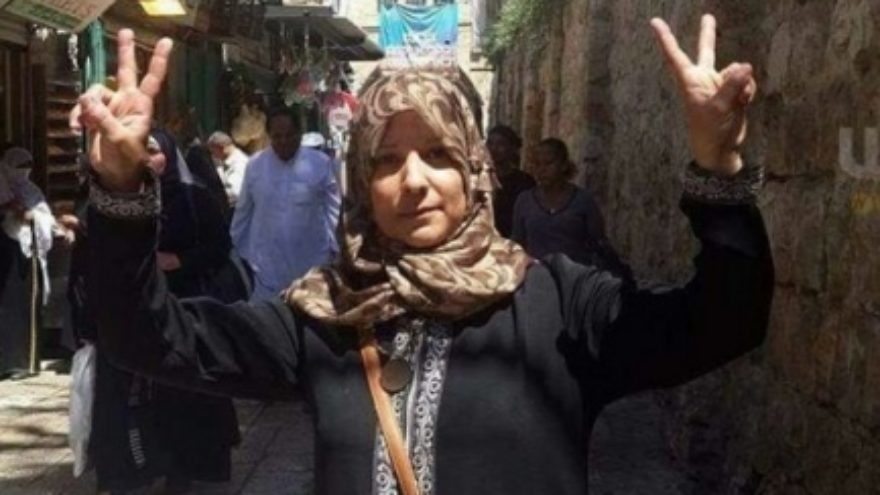 """Click photo to download. Caption: Suhair Halabi flashes """"V"""" for """"Victory"""" signs with both hands at the site where her son, Muhannad, carried out a deadly terrorist attack. Credit: Facebook."""