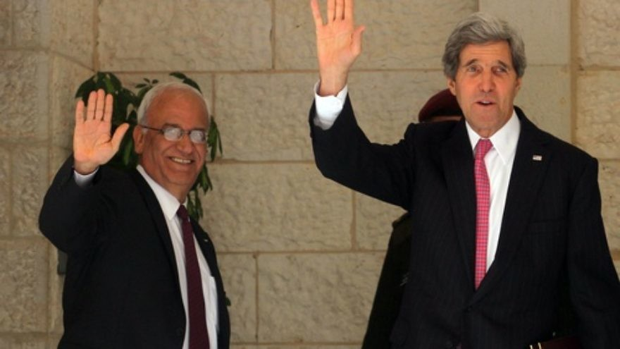 U.S. Secretary of State John Kerry (right) and chief Palestinian negotiator Saeb Erekat wave before a meeting with Palestinian Authority leader Mahmoud Abbas in Ramallah on Jan. 4, 2014. After recent developments, all parties involved may soon be waving goodbye to the Israeli-Palestinian peace negotiations, which have an April 29 deadline for a resolution. Credit: Issam Rimawi/Flash90.