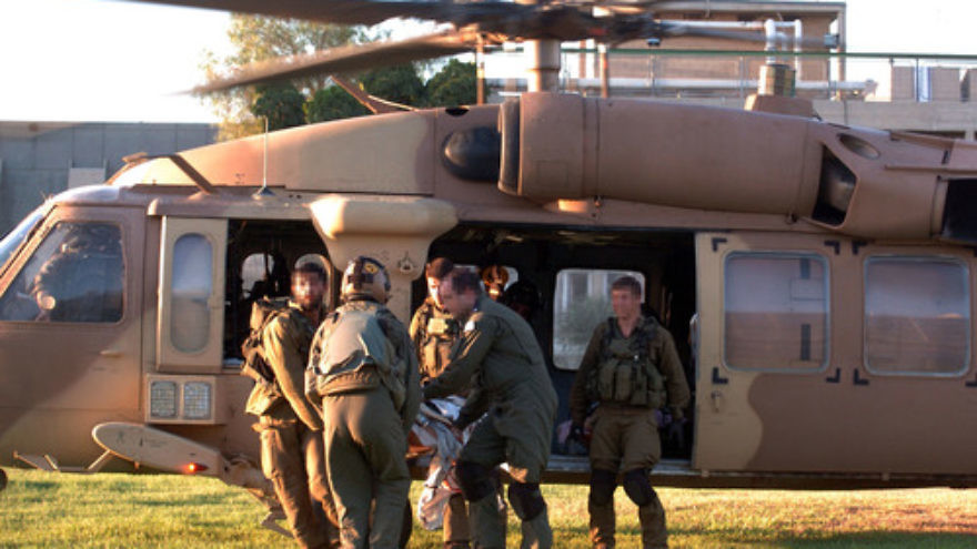 Click photo to download. Caption: IDF soldiers rush injured Israelis to Soroka Hospital in Beersheba after evacuating them by helicopter on Aug. 26, 2014, following a mortar attack on Kibbutz Nirim near the Gaza border. Two Israeli men died from wounds they sustained in the incident, which took place shortly before the latest Israel-Hamas cease-fire deal went into effect. Credit: Flash90.