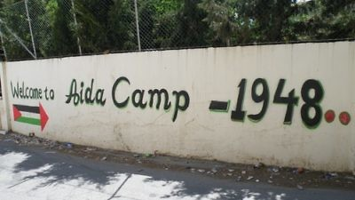 Click photo to download. Caption: The entrance to the Aida Palestinian refugee camp in the West Bank. Credit: Mrbrefast/Wikimedia Commons.