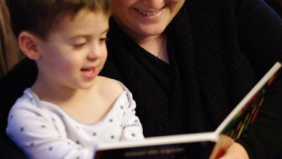 Joy Getnick reading a Hanukkah story book to her son, Benjamin. Credit: Jonathan Getnick.