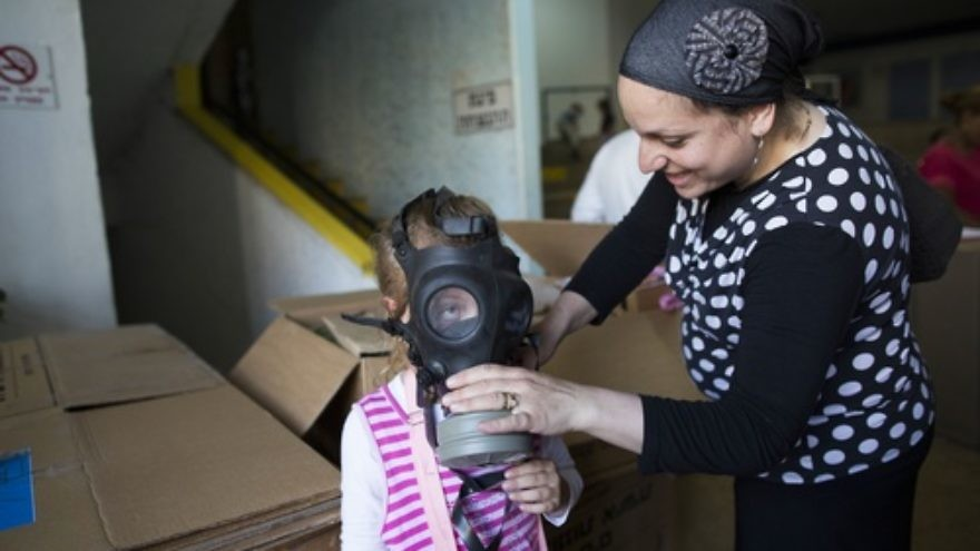 An Israeli woman shows her child how to put on a gas mask at a distribution center in Jerusalem on August 27, 2013. As talks of an international attack on Syria heighten, the demand for gas masks in Israel rose. Credit: Yonatan Sindel/Flash90.