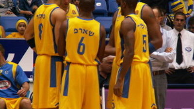 Caption: Basketball players from Maccabi Tel Aviv huddle up.