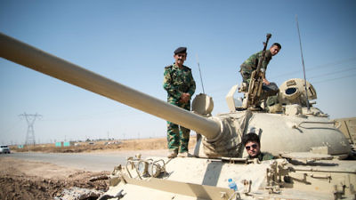 Members of the Kurdish Peshmerga forces on a tank outside Kirkuk, Iraq, in June 2014. Credit: Boris Niehaus via Wikimedia Commons.