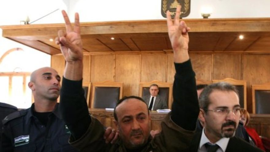 Palestinian terrorist Marwan Barghouti (center) raises his hands in V-for-victory signs in an Israeli courtroom in January 2012. Barghouti was the subject of a controversial advertisement that was printed in The Forward newspaper last month. Credit: Flash90.