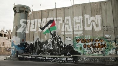 Anti-Israel graffiti on the Israeli security wall in Bethlehem. The wall comes under heavy criticism from those who claim it cuts off Palestinian communities from one another. Credit: Garry Walsh via Wikimedia Commons.