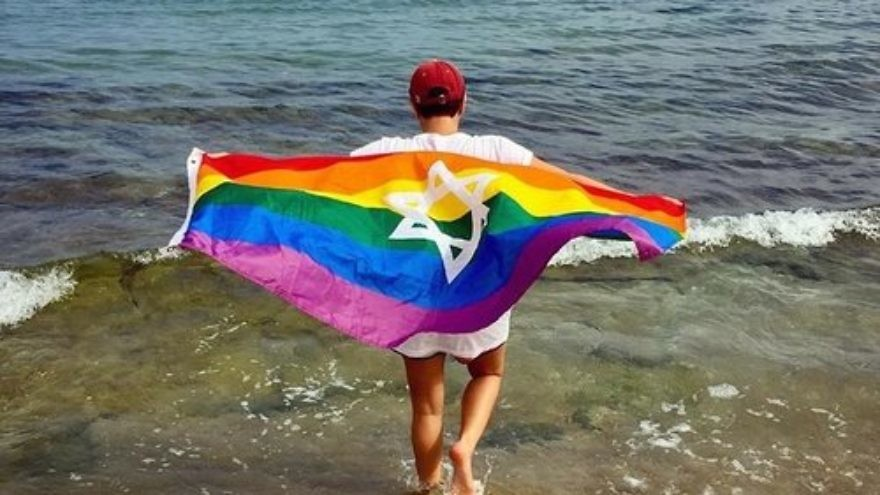 A Birthright Israel trip participant with a Jewish gay pride flag parade on the Hilton Beach in Tel Aviv. Credit: Birthright Israel Facebook page.