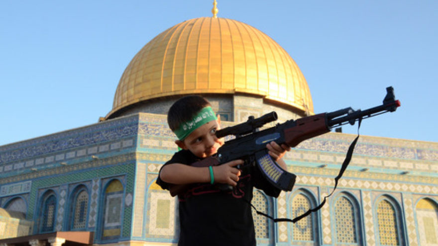 A Palestinian child wearing a Hamas headband aims a toy gun during a rally after Eid prayers at the Al-Aksa mosque in Jerusalem on July 28, 2014. While such scenes are a manifestation of radical Islam, a growing number of pro-Israel Muslims are seeking an alternative path that they hope will lead to peace with the Jewish state. Credit: Sliman Khader/Flash90.