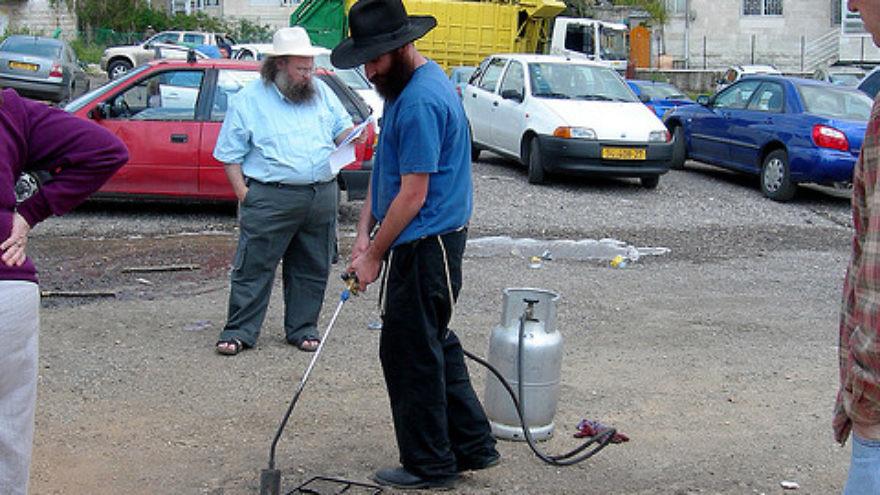 Koshering underway on a Jerusalem street. Credit: Judy Lash Balint.