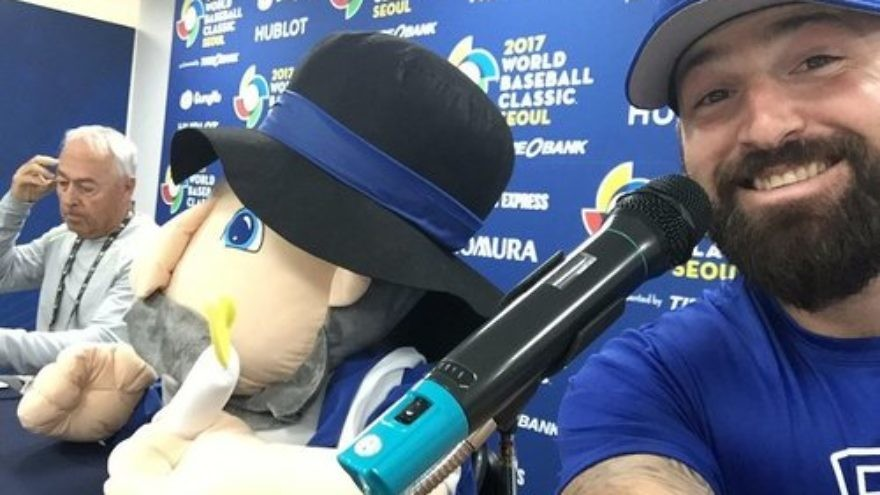 Cody Decker (right), a member of Team Israel at the World Baseball Classic (WBC), poses with the Israeli team's mascot—the Hanukkah toy Mensch on a Bench (center)—at a WBC press conference in March. Credit: Cody Decker via Twitter.