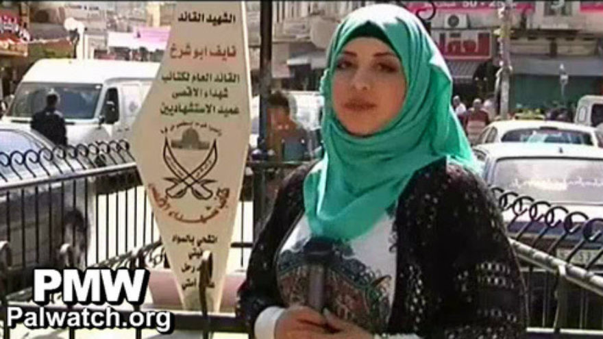 The mother of Palestinian terrorist Naif Abu Sharakh is pictured next to a new monument in a Nablus city square that was renamed after her son. Credit: Palestinian Media Watch.