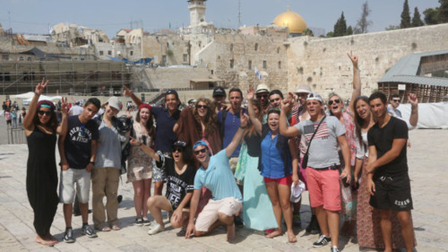 """Taglit-Birthright Israel trip participants visit the Western Wall in the Old City of Jerusalem, Aug. 18, 2014. This photo was published with a recent news report on a J Street-driven letter, in which 575 Jewish students stated that Birthright has a policy of not traveling to """"the West Bank,"""" thus supposedly recognizing """"a distinction"""" between pre-1967 Israel and Jewish settlements beyond the 1967 lines. Columnist Stephen M. Flatow explains the significance of the photo choice. Credit: Flash90."""