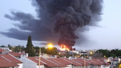 A burning factory in the southern Israeli city of Sderot that was hit by a rocket fired from Hamas-controlled Gaza on June 28, 2014. Credit: Natan Flayer via Wikimedia Commons.