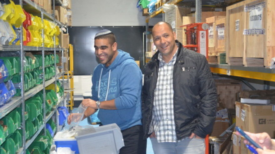 "Click photo to download. Caption: Chen Orpaz (left) with IDF Lt. Col. (Ret.) Ariel Almog, founder of ""Special in Uniform,"" in the warehouse of the Rehovot-based technology company IDEA. Orpaz, who has an intellectual disability, now works at IDEA after picking up the skills he needed from working in the warehouse on an air force base as part of the Special in Uniform project. Credit: Courtesy Jewish National Fund."