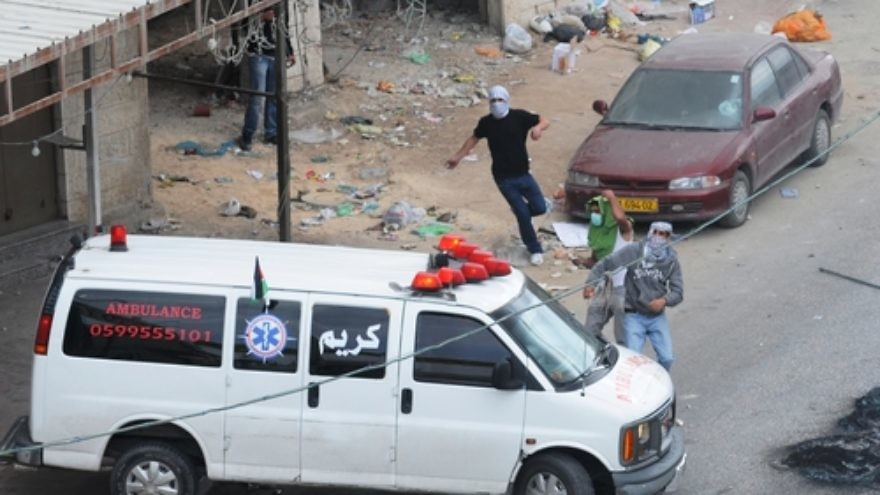 Click photo to download. Caption: Palestinian rioters in Qalandiya use an ambulance for cover as they hurl rocks in May 2011. Credit: Israel Defense Forces.