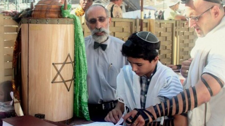 A bar mitzvah boy reads his Torah portion at the Western Wall in Jerusalem. Credit: Peter van der Sluijs via Wikimedia Commons.
