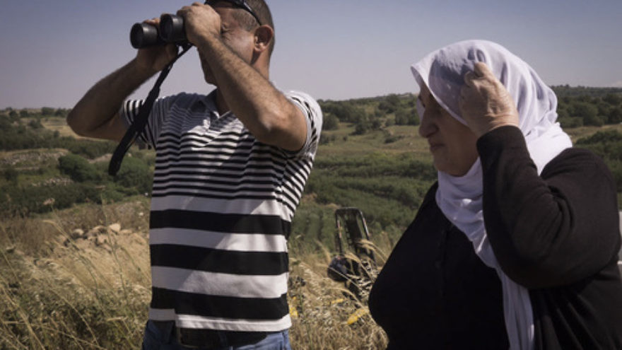 Click photo to download. Caption: Members of the Israeli Druze community watch civil war fighting between Syrian forces from the Israeli side of the Israel-Syria border in the Golan Heights on June 16, 2015. Druze residents of Israel have recently raised concern for the safety of their fellow Druze on the Syrian side. Photo by Basel Awidat/Flash90.