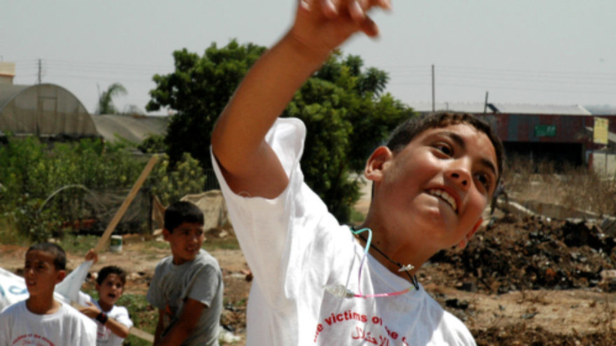 Click photo to download. Caption: A Palestinian boy throws a stone at Israel's security fence. Credit: Justin McIntosh.