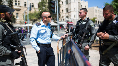 Click photo to download. Caption: An Israeli policeman (second from left) speaks to Israeli soldiers guarding the stairs to the Damascus Gate in Jerusalem's Old City on March 23, 2016. Credit: Corinna Kern/Flash90.