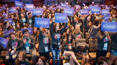 "Delegates hold signs stating ""We Remember"" in five languages at the BBYO International Convention's Friday morning plenary session Feb. 17. Credit: Jason Dixson Photography."