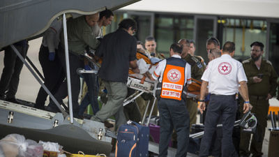 Israeli soldiers and ZAKA emergency response volunteers carry an Israeli upon arrival from Turkey at Ben-Gurion Airport on Sunday. Three Israeli tourists were killed in a suicide-bombing in Istanbul on Saturday. Credit: Hadas Parush/Flash90.