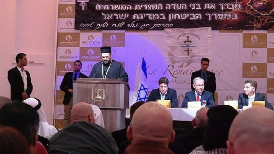 Click photo to download. Caption: Father Gabriel Naddaf addresses Christian IDF soldiers in December 2014, with Israeli Prime Minister Benjamin Netanyahu (sitting at table, in center) in attendance. Credit: Maor X via Wikimedia Commons.