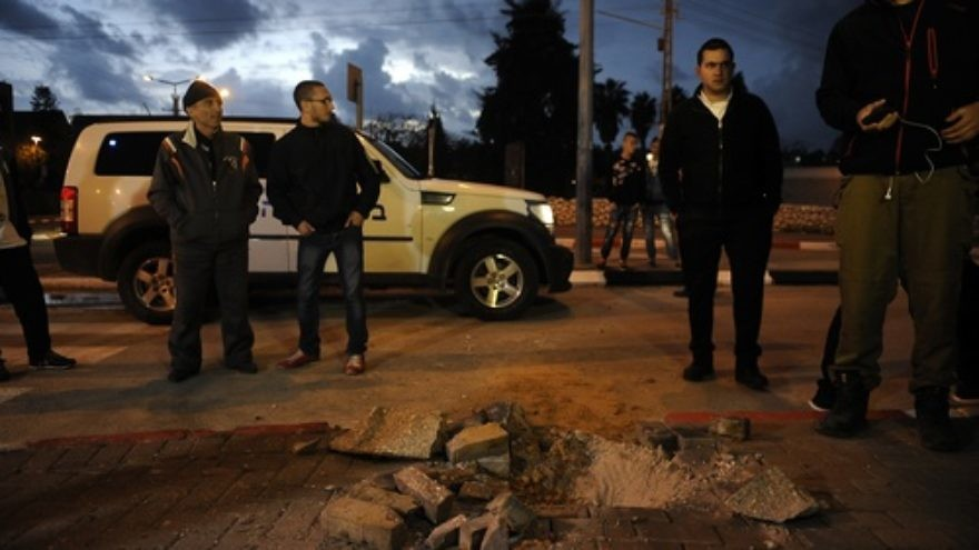 Israelis stand near a hole caused by a Palestinian rocket fired from Gaza into the southern Israeli city of Sdeort on March 12, 2014. At least 60 Islamic Jihad rockets were launched from Gaza at Israel from March 12-13. Credit: Flash90.
