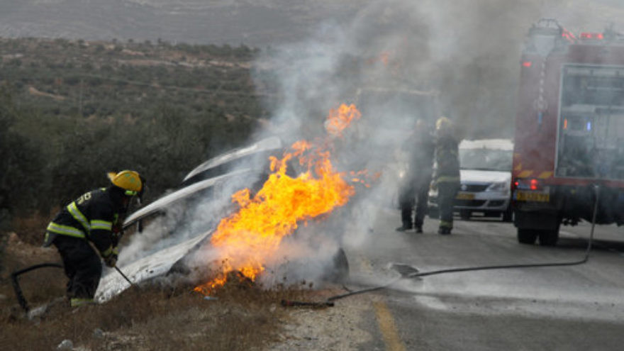 Firefighters put out a blaze from a burning car belonging to Israeli Jews near the West Bank village of Tuqua on Nov. 8, 2013. In the attack, an Israeli woman sustained light-to-moderate wounds, and one of her children was lightly injured, after a firebomb was hurled at their vehicle near Tekoa in Gush Etzion. Credit: Gershon Elinson/Flash90.