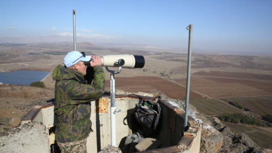 A United Nations observer looks through binoculars at a lookout point on Mount Bental in the Israeli Golan Heights, near the border with Syria, in December 2016. Credit: Yossi Zamir Flash90.
