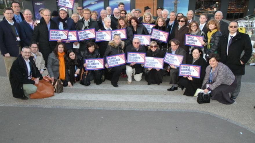 Participants of the Jewish Federations of North America mission to Paris pose in front of the Hyper Cacher kosher grocery in February 2015, where four Jewish shoppers were killed weeks before in an Islamist terror attack. Credit: The Jewish Federations of North America.