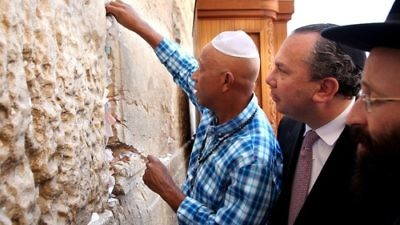 Click photo to download. Caption: Hip-hop mogul Russell Simmons places a note in the Western Wall during his recent trip to Israel. Behind Simmons is his partner for Muslim-Jewish dialogue work, Rabbi Marc Schneier. Credit: Sasson Tiram.