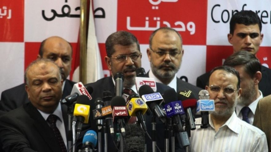 Click photo to download. Caption: Egypt's Muslim Brotherhood presidential candidate Mohammed Morsi (C) speaks during a press conference in Cairo on Monday, June 18. The Muslim Brotherhood claimed victory in Egypt's first presidential election since Hosni Mubarak was ousted more than a year ago. Credit: EPA/AHMED KHALED.