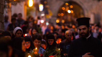 Click photo to download. Caption: Eastern Orthodox Christian nuns hold candles and flowers as they walk along the Via Dolorosa in the Old City of Jerusalem on Aug. 25, 2015. Credit: Micah Bond/Flash90.