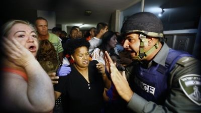 An Israeli border policeman tries to comfort residents in an apartment building after a Grad missile fired by Palestinian terrorists inside the Gaza strip exploded outside their building in Ashdod, Israel, on Oct. 29, 2011. Credit: EPA/EDI ISRAEL.