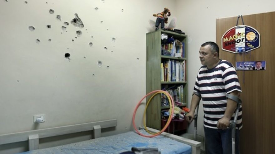 Click photo to download. Caption: An Israeli man examine the damages from the shrapnels in the child room after a long-range Grad rocket fired by Palestinian terrorists from the Gaza Strip landed in the backyard of a house in the southern Israeli town of Netivot, Friday, Oct. 12, 2012. Credit: Tsafrir Abayov/Flash90.