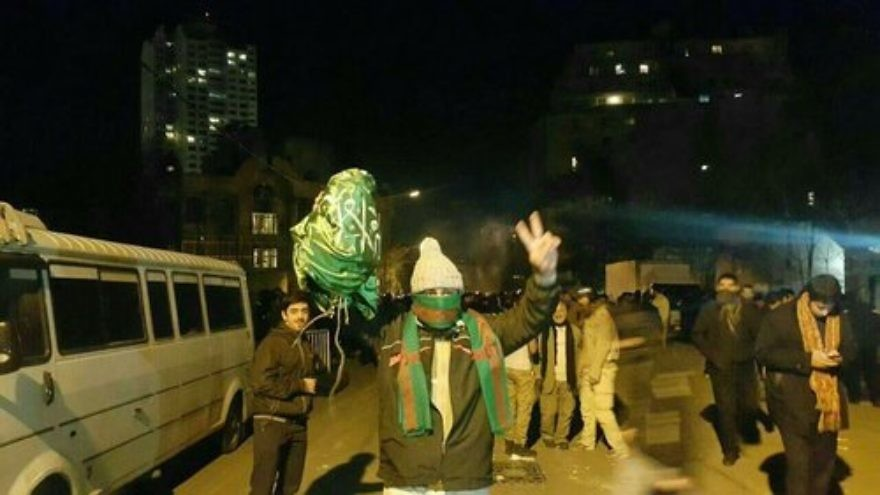 Click photo to download. Caption: Protesters bring down the Saudi flag at the Arab nation's embassy in Tehran, Iran, on Jan. 2. Credit: Sobhan Hassanvand via Twitter.
