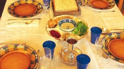 A Passover seder table. Susan Abeles received a five-day suspension for going AWOL from work during Passover, and was later forced into early retirement. Credit: Gilabrand via Wikimedia Commons.
