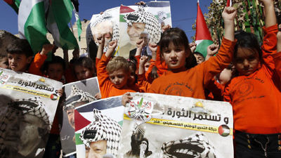 Palestinian children hold posters with the picture of former Palestinian head Yasser Arafat and current Palestinian Authority leader Mahmoud Abbas during a rally in Hebron marking the 12th anniversary of Arafat's death Nov. 10, 2016. Credit: Wisam Hashlamoun/Flash90.
