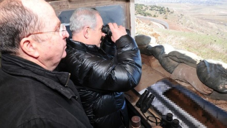 Israeli Minister of Defense Moshe Ya'alon (left) and Prime Minister Benjamin Netanyahu (center, with binoculars) survey the Israeli-Syrian border in the strategically significant Golan Heights region on Feb. 18, 2014. Credit: Ariel Hermoni/Ministry of Defense/FLASH90.