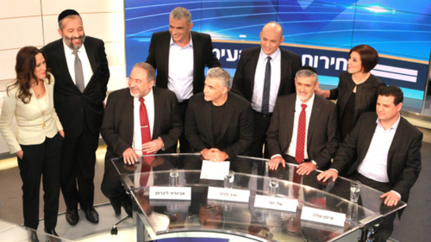 Pictured at the Feb. 26 Israeli election debate hosted by Israel's Channel 2 network: Yisrael Beiteinu Party leader Avigdor Lieberman (bottom left); Yesh Atid Party leader Yair Lapid (bottom, second from left); Yachad Party leader Eli Yishai (bottom, second from right); Joint Arab List Party leader Ayman Odeh (bottom right); Meretz Party leader Zehava Gal-On (top right); Shas Party leader Aryeh Deri (top, second from left); Habayit Hayehudi Party leader Naftali Bennett (top, second from right); Kulanu Party leader Moshe Kahlon (top, center); and Channel 2 news anchor Yonit Levi (top left). Credit: Channel 2 News.