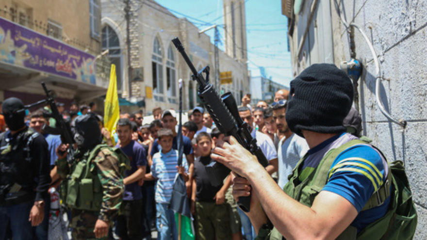 Click photo to download. Caption: A crowd of Palestinians, including some who are armed and masked, in the Qalandiya refugee camp on July 3, 2015. Credit: Flash90.
