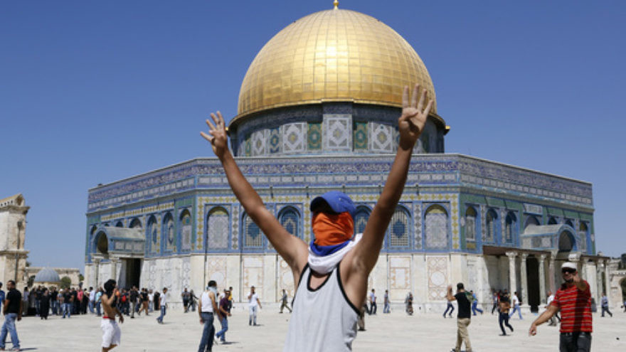 "Click photo to download. Caption: A Palestinian rioter raises his hands in a ""V"" pose, for ""victory,"" near the Dome of the Rock mosque on the Temple Mount holy site in Jerusalem. Credit: Sliman Khader/Flash90."