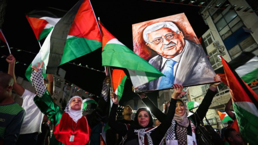 Palestinians in Ramallah wave their national flags and a picture of Palestinian Authority leader Mahmoud Abbas while they watch a live-screening of Abbas's speech at the United Nations on Sept. 30, 2015. Photo by Flash90.