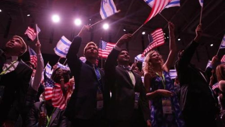 Attendees of the 10th Christians United for Israel (CUFI) Washington Summit wave Israeli and American flags, July 13, 2016. Credit: CUFI via Facebook.