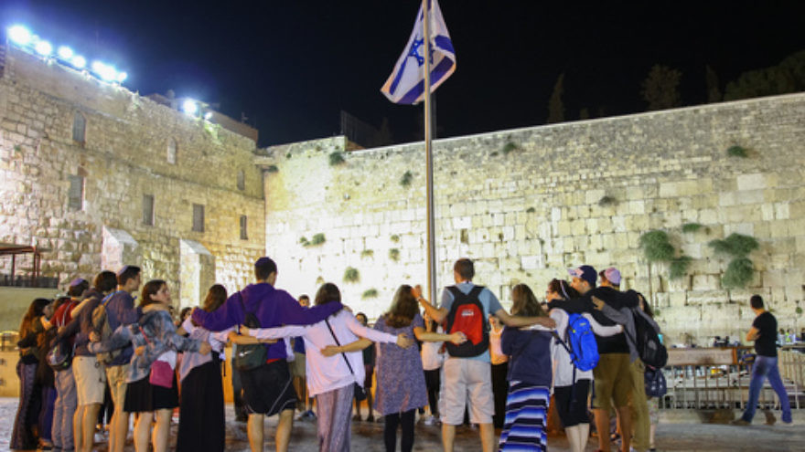 Participants of Ramah's Israel summer-camp experience stand arm in arm at the Western Wall in Jerusalem. Credit: Ramah Commission.
