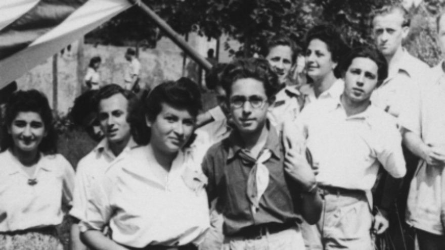 Click photo to download. Caption: Akiva Kohane (front, wearing dark shirt) and a group of friends pose with a Zionist flag during a sports day in Tradate Italy. Kohane was a Haganah member during Israel's War of Independence. Credit: United States Holocaust Memorial Museum.